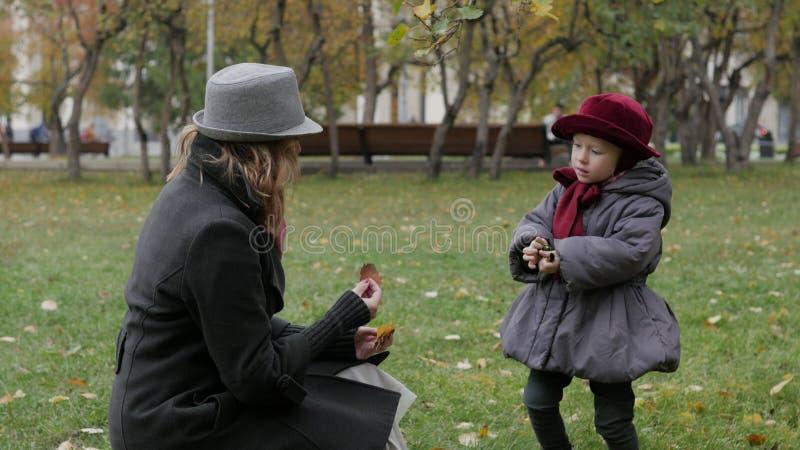 妈妈和女儿在演奏投掷的叶子的公园 图库摄影