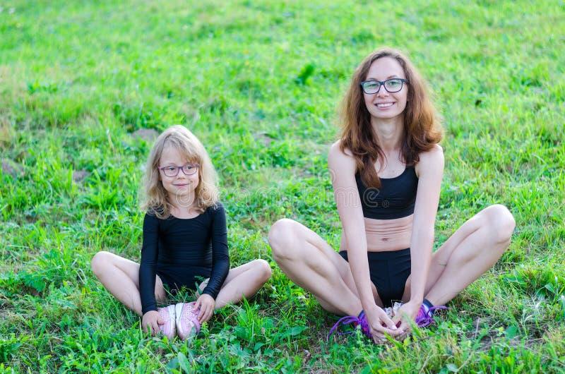 妈妈和女儿在莲花坐坐本质上 免版税图库摄影