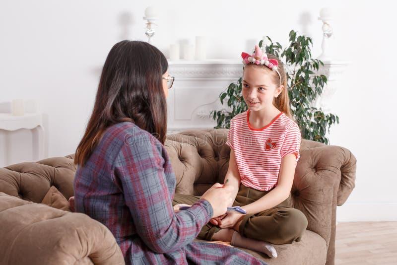 妈妈和女儿坐长沙发和聊天 女孩少年激动讲她的母亲故事 女儿分享她 库存图片