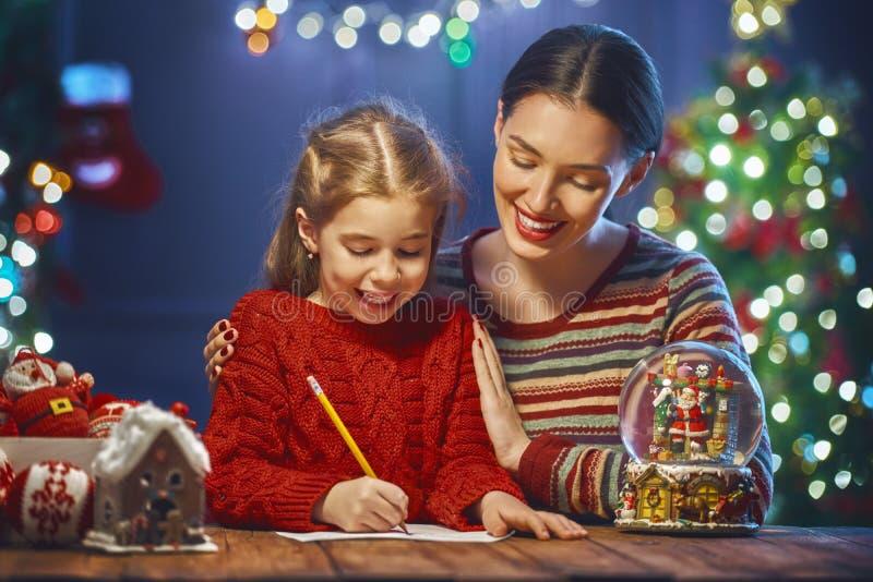 妈妈和女儿对圣诞老人的文字邮件 免版税库存照片