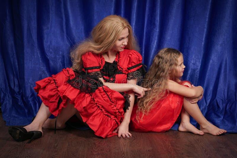 妈妈和女儿是被触犯和坐地板 妈妈设法建立和平和友谊与孩子 免版税图库摄影