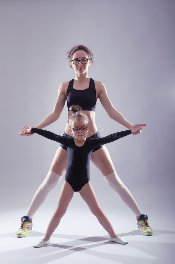 妈妈和女儿游泳衣跳舞的在灰色背景 免版税图库摄影