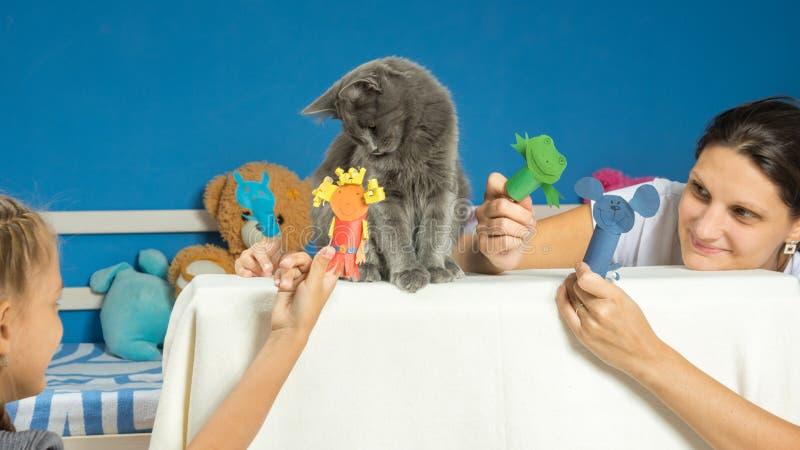 妈妈和女儿演奏有一只疲乏的猫的木偶剧院 库存照片