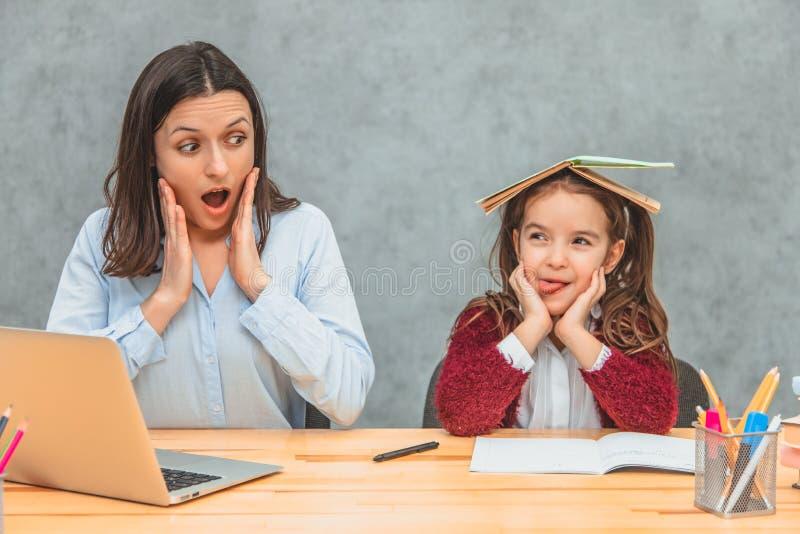 妈妈和女儿灰色背景的 在此期间,女孩在书上把一本开放书放并且显示舌头 ?? 免版税库存照片