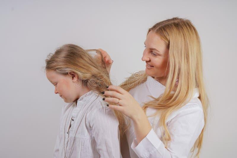妈妈和女儿白色衬衫的有摆在坚实背景的长的金发的在演播室 一个迷人的家庭照料  库存图片