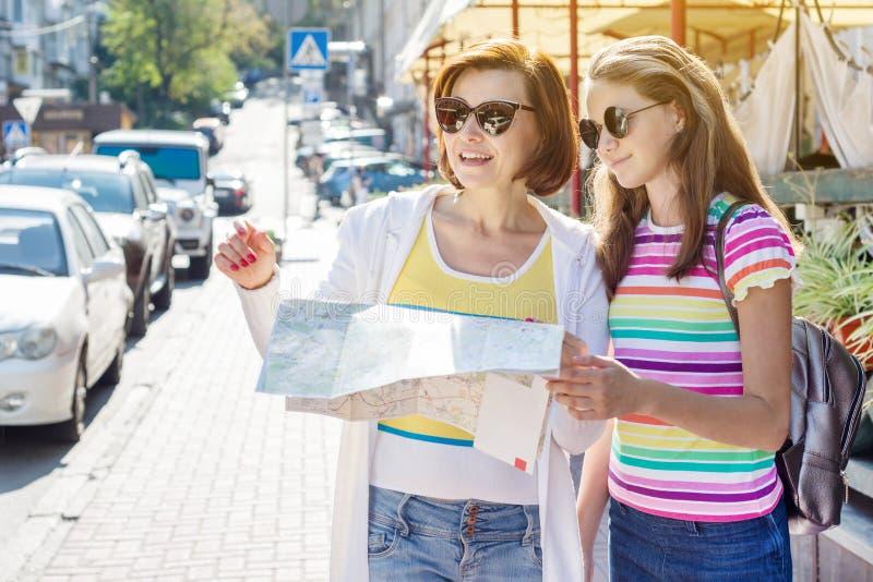 妈妈和女儿看在欧洲城市街道上的少年游人地图  免版税库存图片