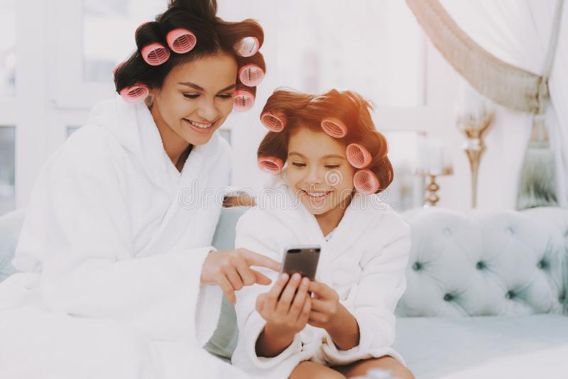 妈妈和女儿看看在蓝色沙发的电话在温泉 库存图片