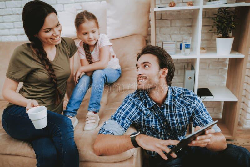 妈妈和女儿看看有黑片剂的父亲 库存图片