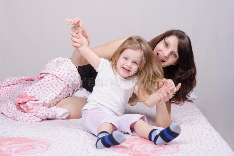 妈妈和女儿获得乐趣在三年床 图库摄影