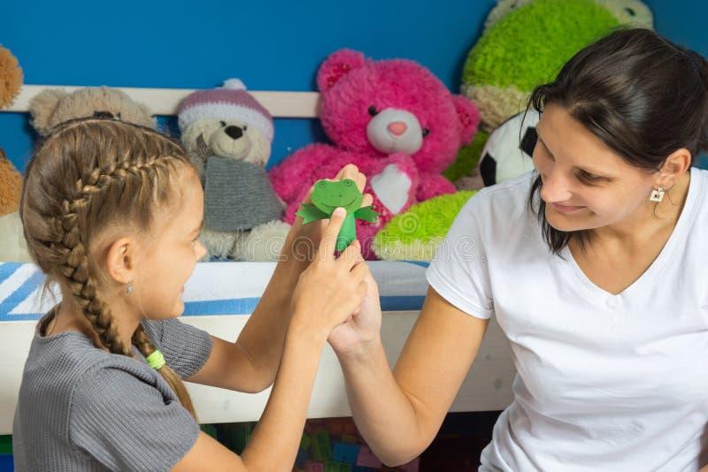 妈妈和女儿黏附一个头到青蛙的纸手指小雕象 图库摄影