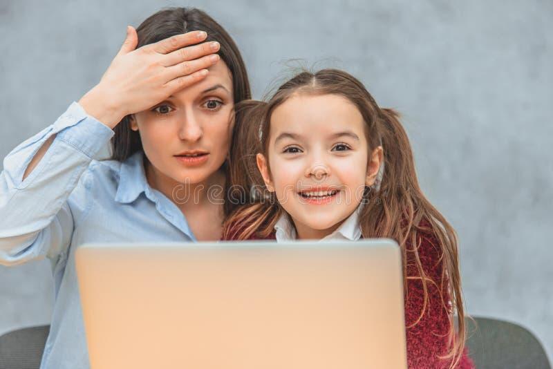 妈妈和女小学生坐在桌上 两个调查一台灰色膝上型计算机 震动的妻子投入她的手 库存图片