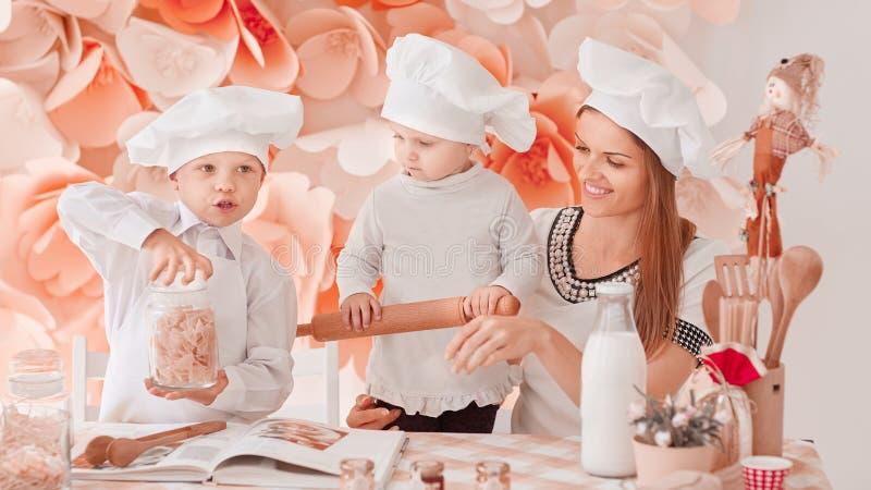 妈妈和她的两个小孩一起烹调晚餐 库存照片