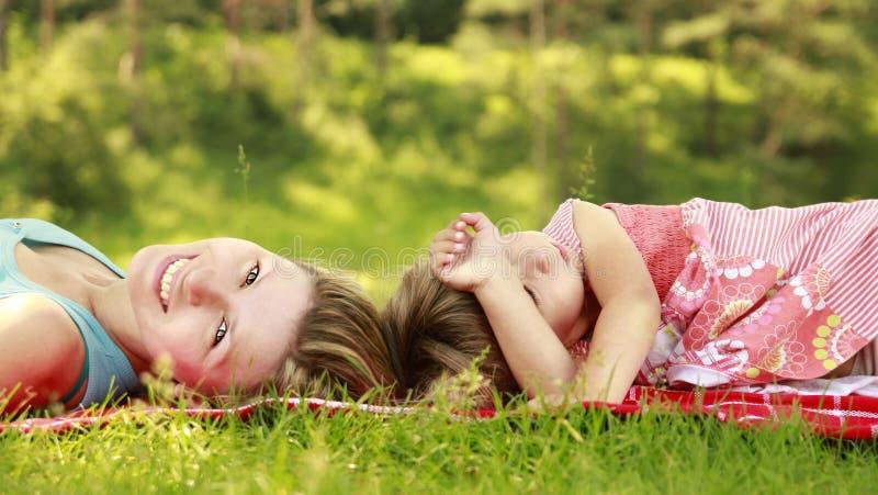 妈妈和她的小女儿在草说谎 库存图片