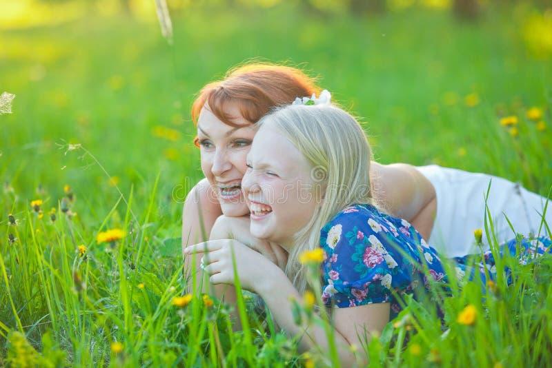 妈妈和她的小女儿在草说谎 免版税图库摄影