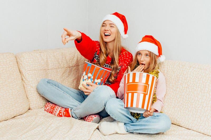 妈妈和她的小女儿,打扮在圣诞老人项目帽子,手表 图库摄影