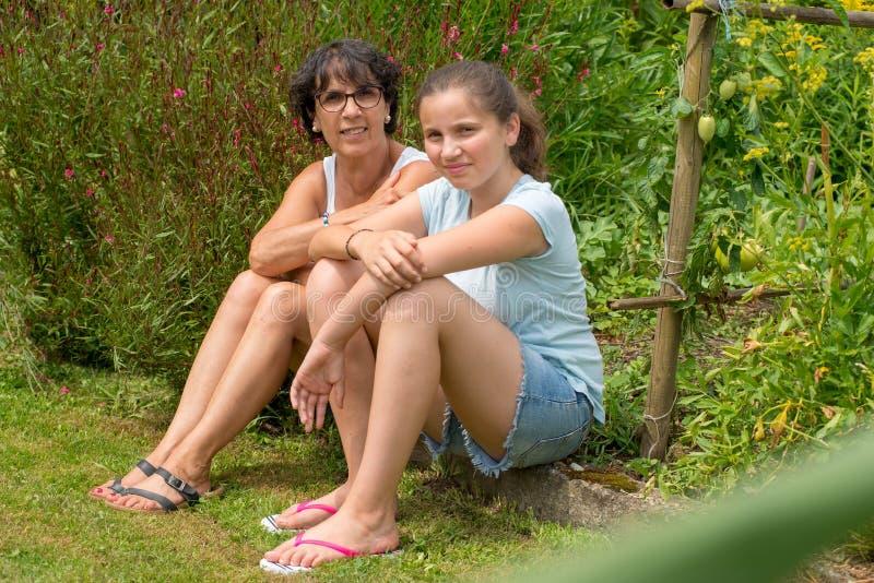 妈妈和她青少年的女儿在草坐 免版税库存照片