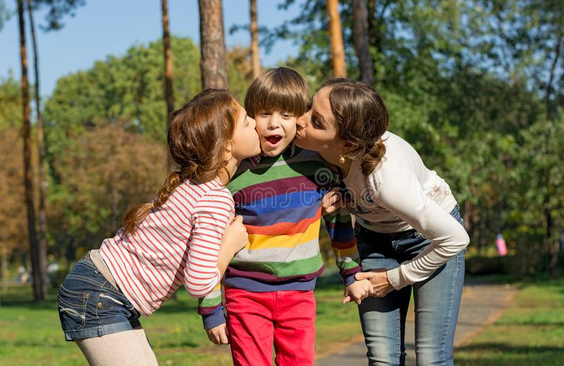妈妈和姐妹亲吻从双方的男孩 库存图片