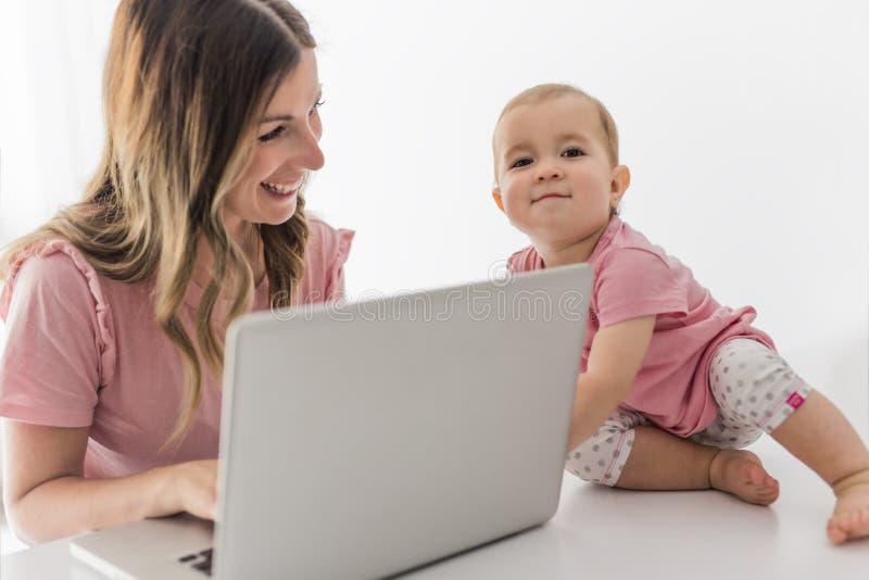 妈妈和婴孩有运转从家的便携式计算机的 免版税库存照片