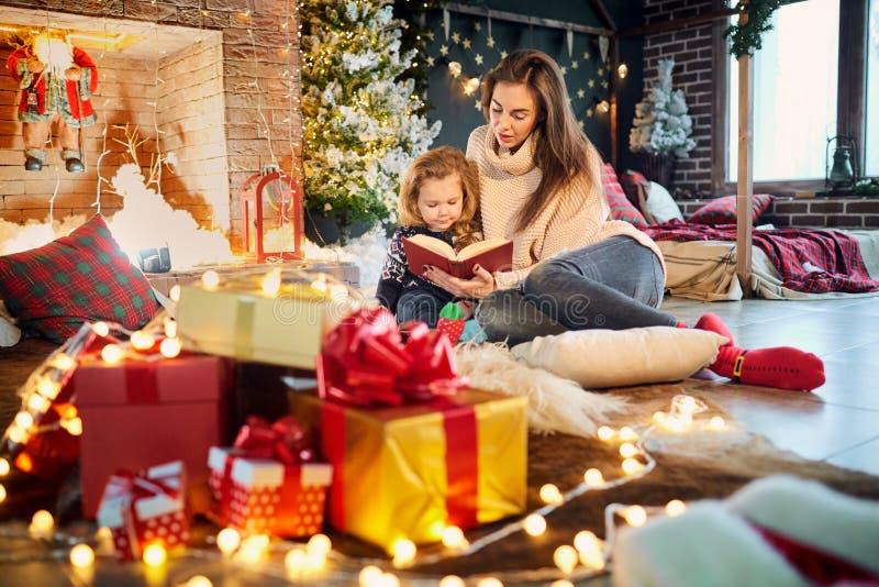 妈妈和孩子在圣诞节读一本书 免版税图库摄影