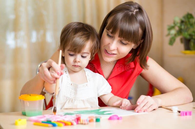 妈妈和孩子在家一起女孩油漆 免版税库存照片