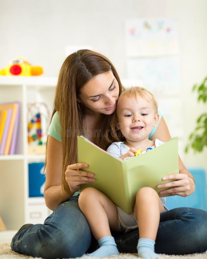 妈妈和孩子男孩在家读了一本书 免版税库存照片