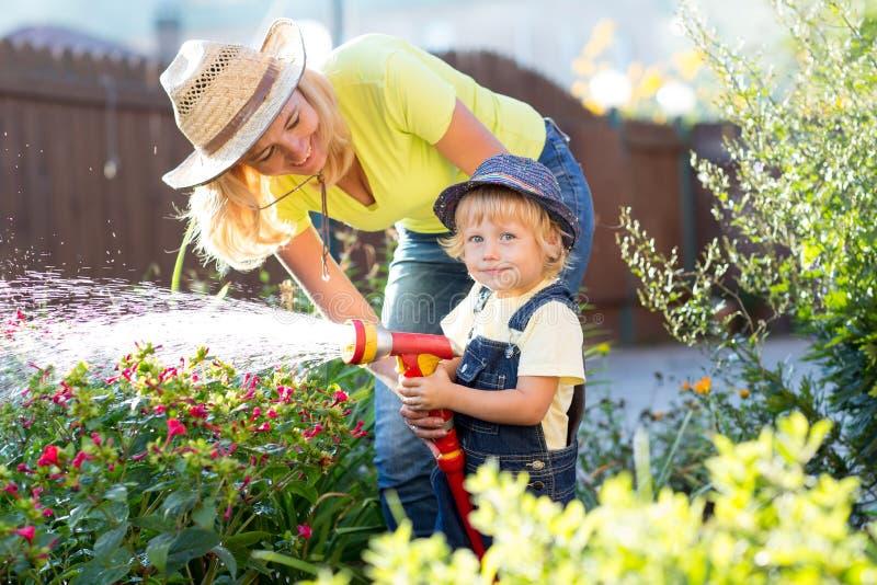 妈妈和小儿子浇灌的花在庭院里 免版税库存照片