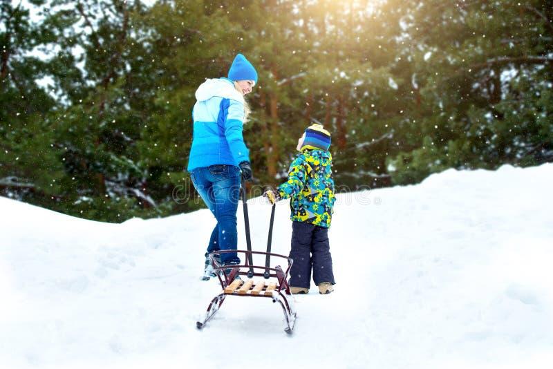 妈妈和小儿子,去与雪撬小山乘坐 冬天乐趣为家庭圣诞节假期 免版税图库摄影