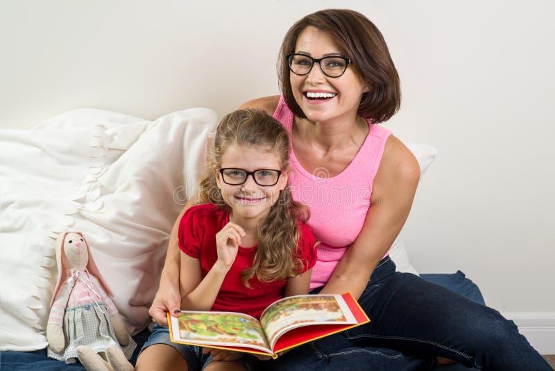 妈妈和小女儿在家读了书在床上 免版税库存图片