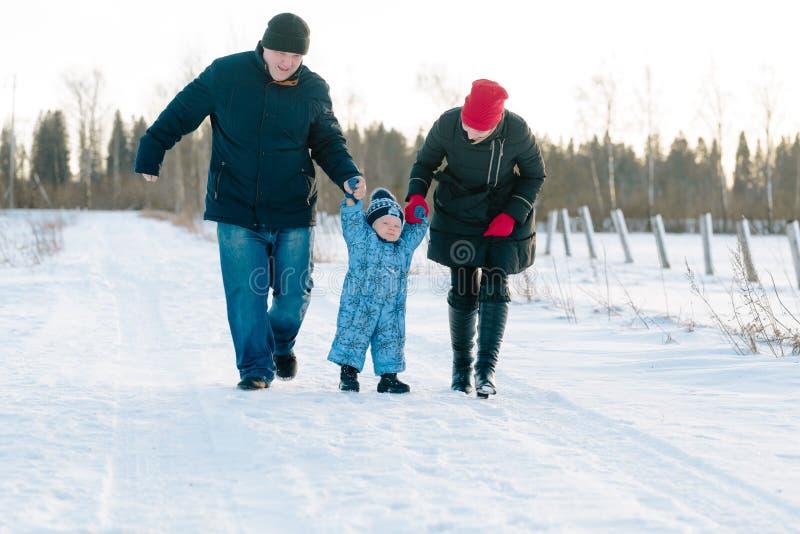 妈妈和爸爸举行婴孩` s手在冬天公园走 免版税库存图片