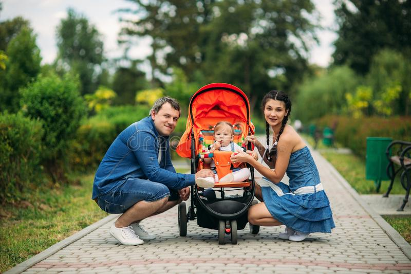 妈妈和爸爸在与一个婴孩的pakr走婴孩车的 免版税库存照片