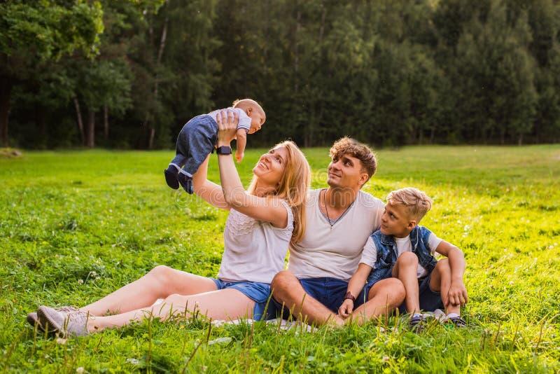 妈妈和爸爸有他们的休息和使用户外在城市之外的两个孩子的 库存图片