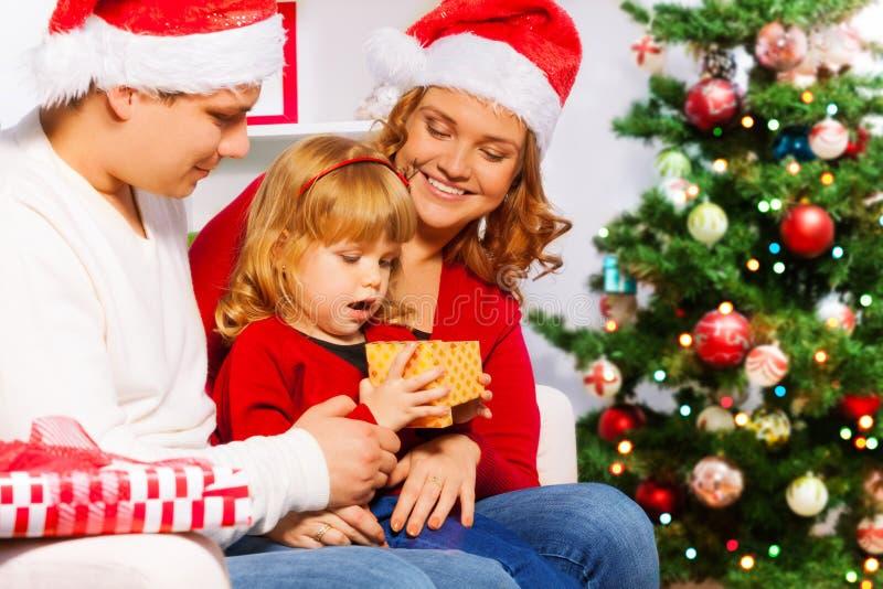 妈妈和爸爸给新年礼物愉快的女孩 库存图片