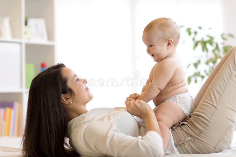 妈妈和男婴使用在晴朗的屋子里的尿布的 的母亲和在家放松的小孩 一起有系列的乐趣 免版税库存图片