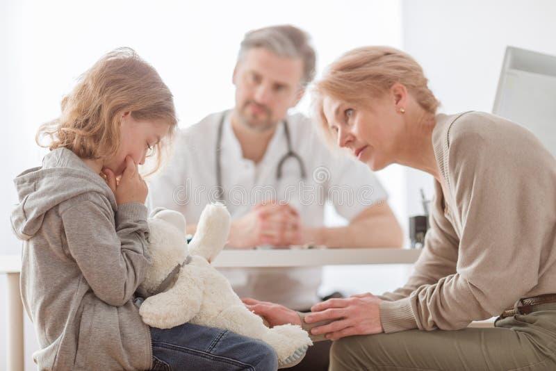 妈妈和逗人喜爱的儿子在儿科医生的书桌前面 图库摄影