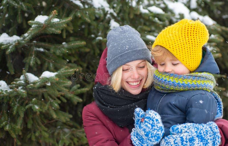 妈妈和逗人喜爱的儿童温暖的帽子围巾 E 使用与孩子冬日的愉快的女孩 享受冬天 免版税库存照片