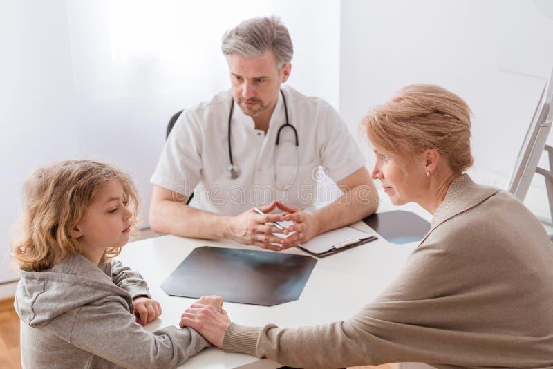妈妈和逗人喜爱的病的儿子在英俊的儿科医生的书桌前面 库存照片