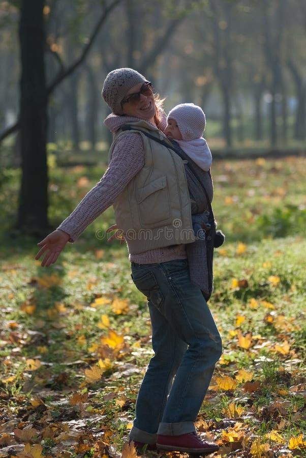 妈妈和婴孩吊索的高兴落的秋叶 库存图片
