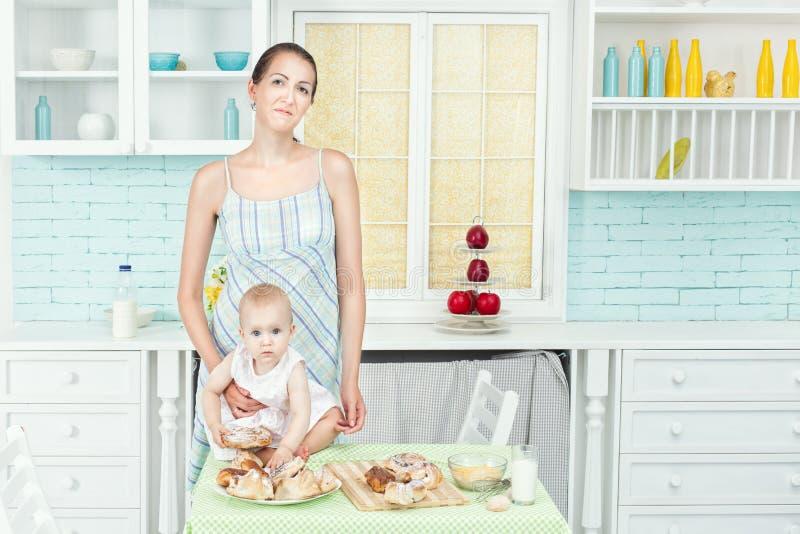 妈妈和婴孩在厨房用桌上 库存照片