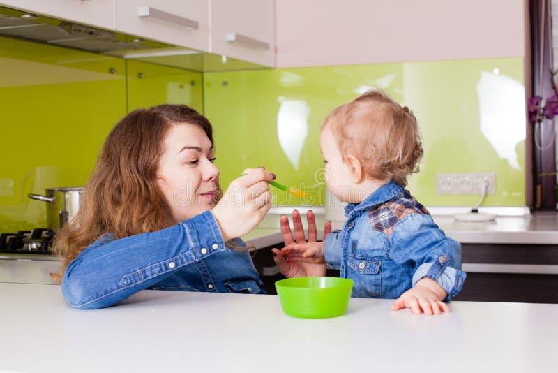 妈妈喂养她的孩子 免版税库存图片
