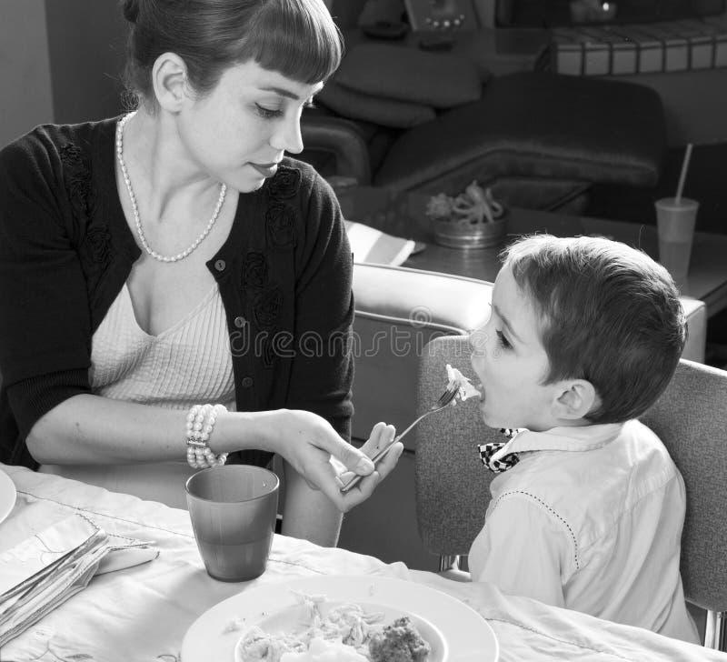 妈妈喂养她的感恩火鸡的儿子 库存图片