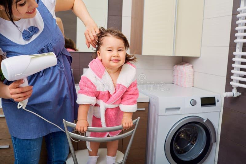 妈妈在卫生间里烘干他的女儿的头发一hairdryer 免版税图库摄影