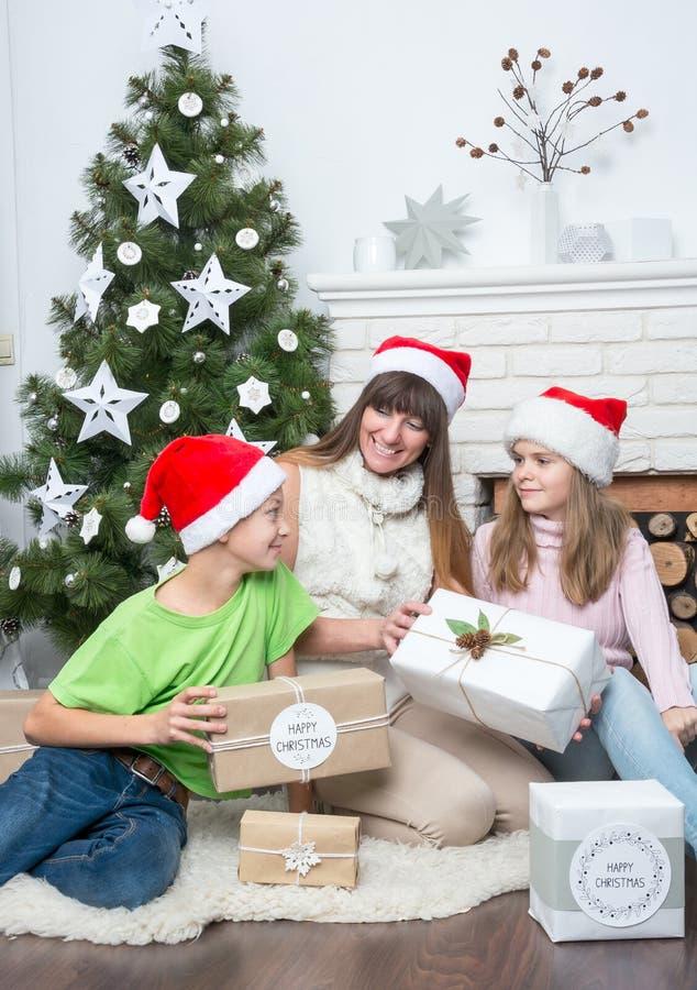 妈妈在圣诞树附近给孩子礼物 免版税库存图片