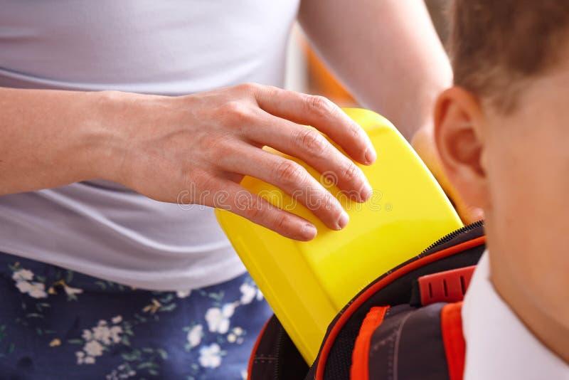 妈妈在她的儿子的一个塑料盒投入被包装的学校午餐 库存图片