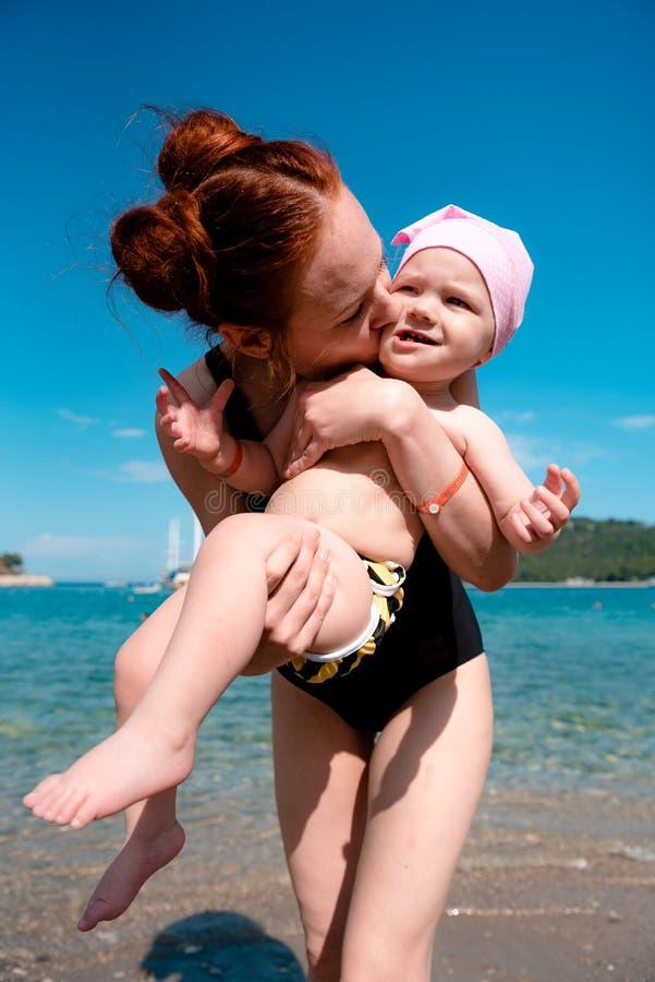 妈妈在面颊a拿着她的她的胳膊的女儿并且亲吻她 库存图片