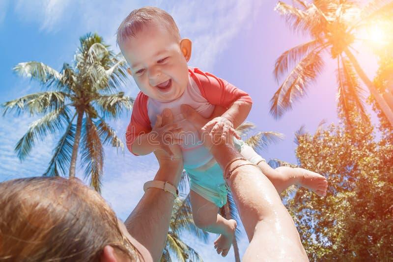 妈妈培养了在她的头上的婴孩 非常一件游泳衣的愉快和笑的孩子在妈妈的胳膊 反对的底视图 免版税库存图片