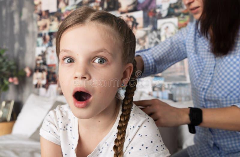 妈妈小心地把她在辫子的心爱的女儿的头发编成辫子在她的头 图库摄影