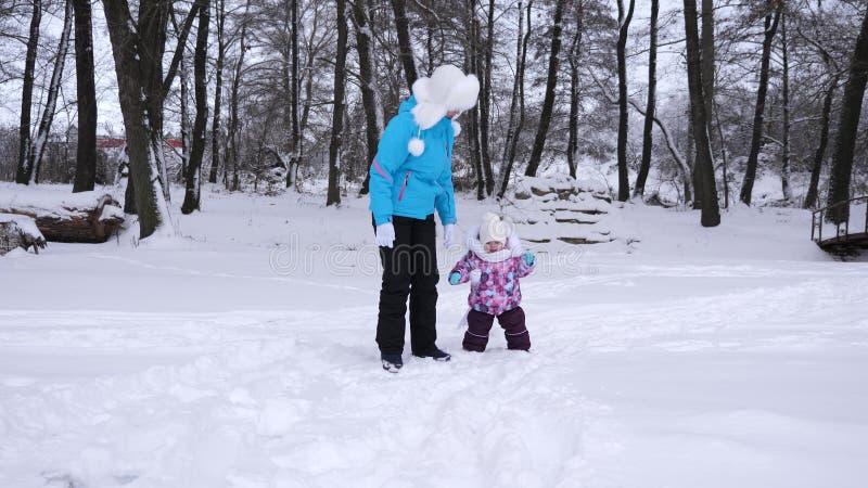妈妈带领她的小女儿的手在步行期间通过积雪的公园在冬天 与是的孩子的母亲步行 图库摄影
