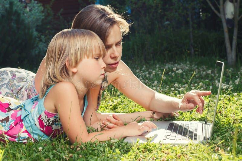 妈妈帮女儿在家里使用笔记本电脑 免版税库存照片