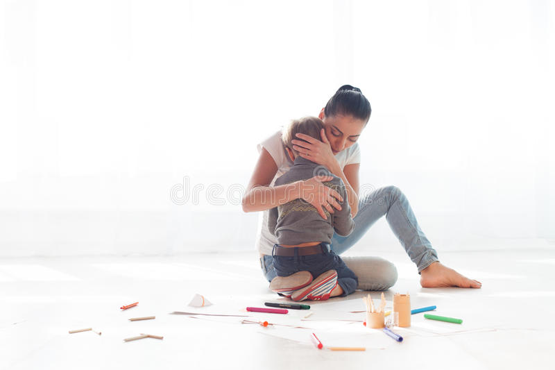 妈妈拥抱她的儿子悲伤爱 免版税库存图片