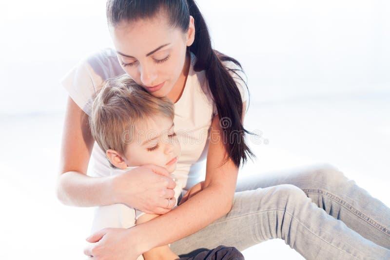 妈妈拥抱她的儿子悲伤爱 库存照片